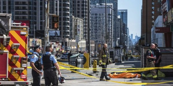 Van jumps sidewalk in Toronto, killing at least 9 pedestrians and injuring 16; police say driver is in custody