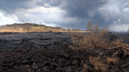 Farmers work next to lava flow
