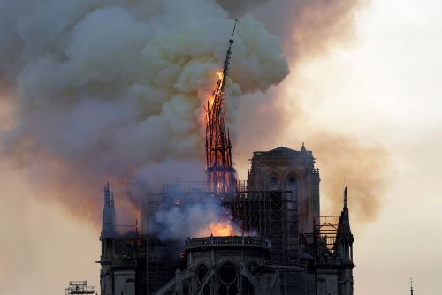 Notre Dame cathedral spire falls as fire rages
