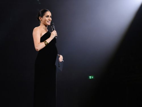 Meghan Markle cradled her growing baby bump in a surprise appearance at the British Fashion Awards in London