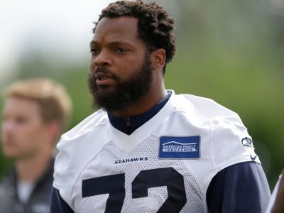 Seahawks defensive end Michael Bennett sits during national anthem in wake of violence in Charlottesville