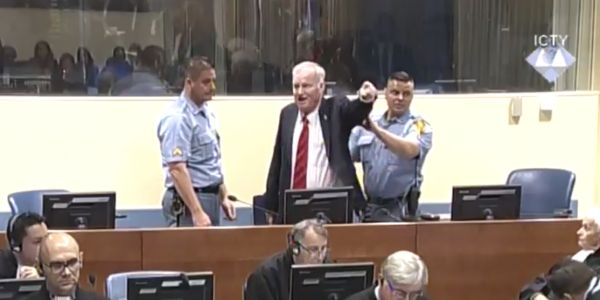 One of Europe's most reviled war criminals was thrown out of court for shouting at a judge moments before being sentenced to life in prison for genocide