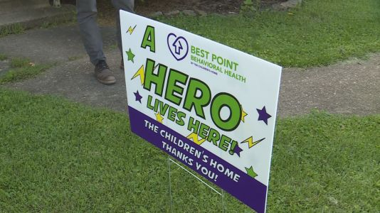 Kids mental health organization surprises therapists, staff with 'A Hero Lives Here' yard signs