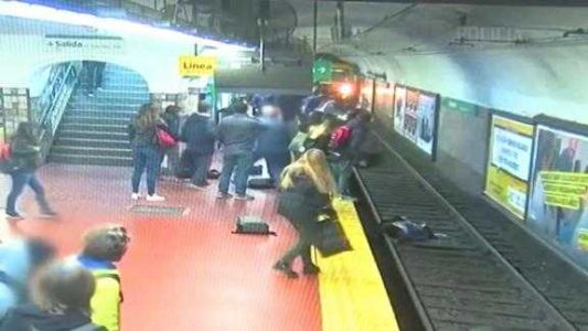 Moment woman falls onto subway tracks and is pulled to safety