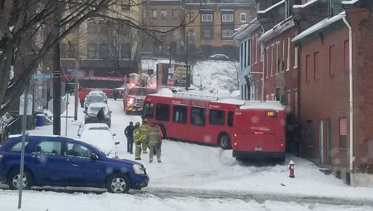 Port Authority bus jackknifes into rowhouse on slick, snow-covered road in uptown Pittsburgh