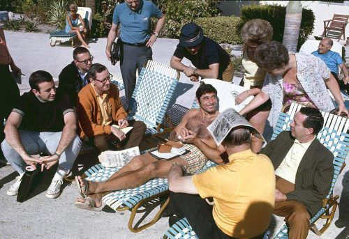 New York Jets quarterback Joe Namath sits by the beach with fans