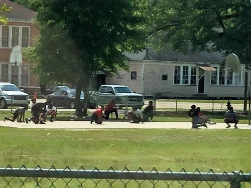 A photo of teens kneeling for a funeral procession has gone viral