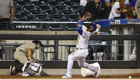 Mets' Jonathan Villar has to dodge balls rolling along Padres' dugout as he chases popup