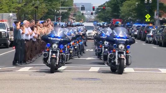 Somber procession brings fallen officer to funeral home